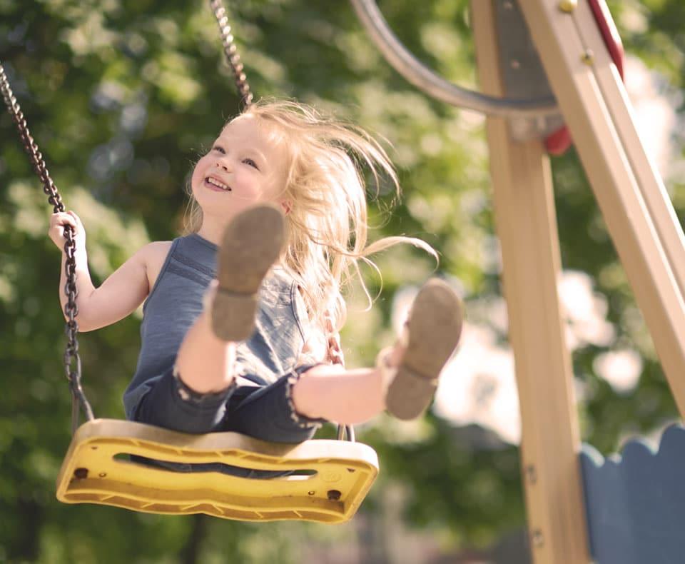 Bambina su altalena in parco giochi